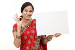 Femme traditionnelle tenant un panneau d'affichage vide photos stock