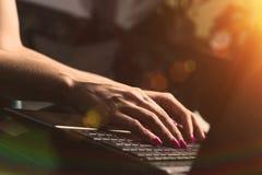 Femme travaillant à la maison, dactylographiant sur un clavier d'ordinateur portable image stock