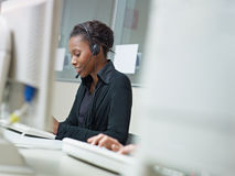 Femme travaillant au centre d'attention téléphonique Images stock
