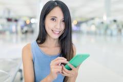 Femme travaillant au téléphone portable dans l'aéroport Photographie stock