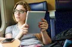 Femme travaillant au train avec des périphériques mobiles Images libres de droits