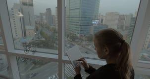 Femme travaillant aux affaires avec la protection à côté de la fenêtre avec la vue de Séoul, Corée du Sud banque de vidéos