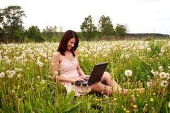 Femme travaillant avec l'ordinateur portatif sur le vert Photographie stock libre de droits