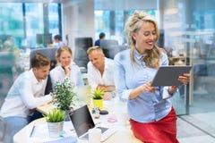Femme travaillant avec la tablette dans le bureau Photo stock