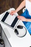 Femme travaillant avec un comprimé numérique Image stock