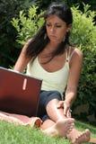 Femme travaillant dans l'ordinateur portatif de nature photo stock
