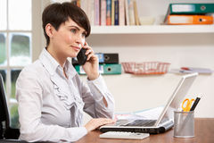 Femme travaillant de la maison utilisant l'ordinateur portatif au téléphone Photos stock
