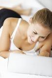 Femme travaillant de son lit Photos libres de droits