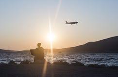 Femme travaillant sur l'ordinateur portable avec le coucher du soleil à la plage Photographie stock