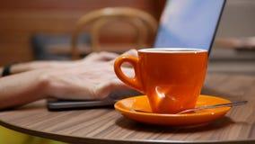 Femme travaillant sur un ordinateur portable avec une tasse de café sur la table, travail éloigné d'un café Concept de travail in banque de vidéos