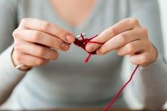 Femme tricotant avec le crochet de crochet et le fil rouge Photographie stock