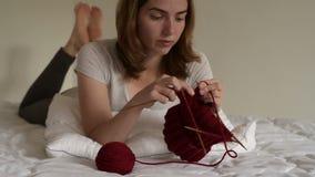 Femme tricotant sur un lit banque de vidéos