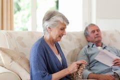 Femme tricotant tandis que son mari dort Photo libre de droits