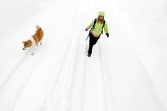 Femme trimardant avec le crabot sur la route et la neige de l'hiver Image stock