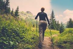 Femme trimardant dans la forêt de montagne Photographie stock