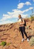 Femme trimardant dans les montagnes rocailleuses de désert Photos stock