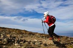 Femme trimardant en montagnes Photo stock