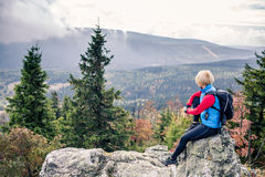 Femme trimardant en montagnes et bois d'automne Images stock