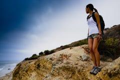 Femme trimardant sur des falaises d'océan Images libres de droits