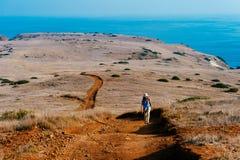 Femme trimardant sur l'île avec l'océan à l'arrière-plan photographie stock