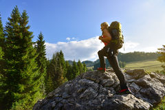 Femme trimardant sur la roche avec le sac à dos Photographie stock libre de droits
