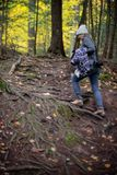Femme trimardant sur la traînée de forêt dans la chute photographie stock libre de droits