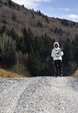 Femme trimardant sur une route de campagne Photos libres de droits
