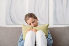 Femme triste étreignant un oreiller image libre de droits