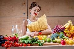 Femme triste avec l'oreiller observant à la nourriture image stock