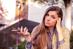 Femme triste contrariée avec l'extérieur debout de téléphone portable dans la rue avec un fond urbain photographie stock