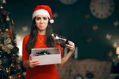 Femme triste détestant recevant les chaussures plates comme cadeau de Noël Images libres de droits