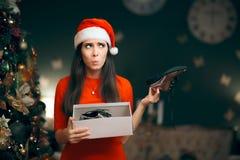 Femme triste détestant recevant les chaussures plates comme cadeau de Noël Image libre de droits