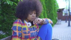 Femme triste d'afro-américain de portrait avec une coiffure Afro se reposant sur un banc sur la rue clips vidéos
