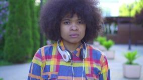 Femme triste d'afro-américain de portrait avec une coiffure Afro sur la rue banque de vidéos