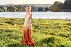 Femme triste dans une longue robe fascinante au coucher du soleil Beaux yeux de tristesse de regard de fille Belles vues de paysa images libres de droits