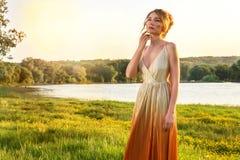 Femme triste dans une longue robe fascinante au coucher du soleil Beaux yeux de tristesse de regard de fille Belles vues de paysa photos libres de droits