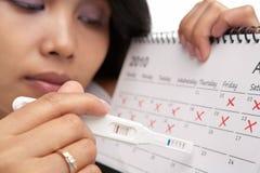 Femme triste, essai de grossesse négatif et calendrier Photos libres de droits