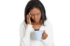 Femme triste fatiguée regardant la tasse de café d'isolement photos stock