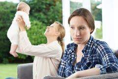 Femme triste jalouse de l'ami avec le jeune bébé Photographie stock libre de droits