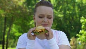 Femme triste mangeant l'hamburger avec dégoût, manque de volonté, dépendance d'aliments de préparation rapide clips vidéos