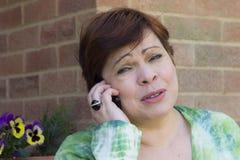 Femme triste parlant au téléphone dehors Image stock