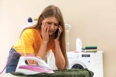 Femme triste parlant au téléphone tout en repassant des vêtements dans la salle de bains photos libres de droits