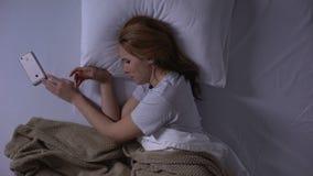 Femme triste pleurant lisant de vieux messages sur le smartphone se situant dans le lit, souvenirs clips vidéos