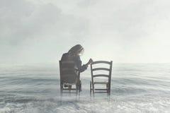 Femme triste regardant avec nostalgie sa chaise vide du ` s d'amant photo stock