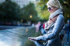 Femme triste regardant les noms du mémorial de World Trade Center image libre de droits