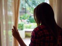 Femme triste regardant une fenêtre, à l'intérieur image stock