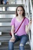 Femme triste sérieuse avec de longs cheveux et yeux bleus, portant T rose image libre de droits