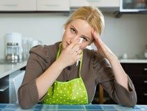 Femme triste s'asseyant à la cuisine Image stock