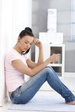 Femme triste s'asseyant sur l'étage à la maison Image stock
