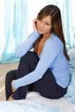 Femme triste s'asseyant sur son lit Photo stock